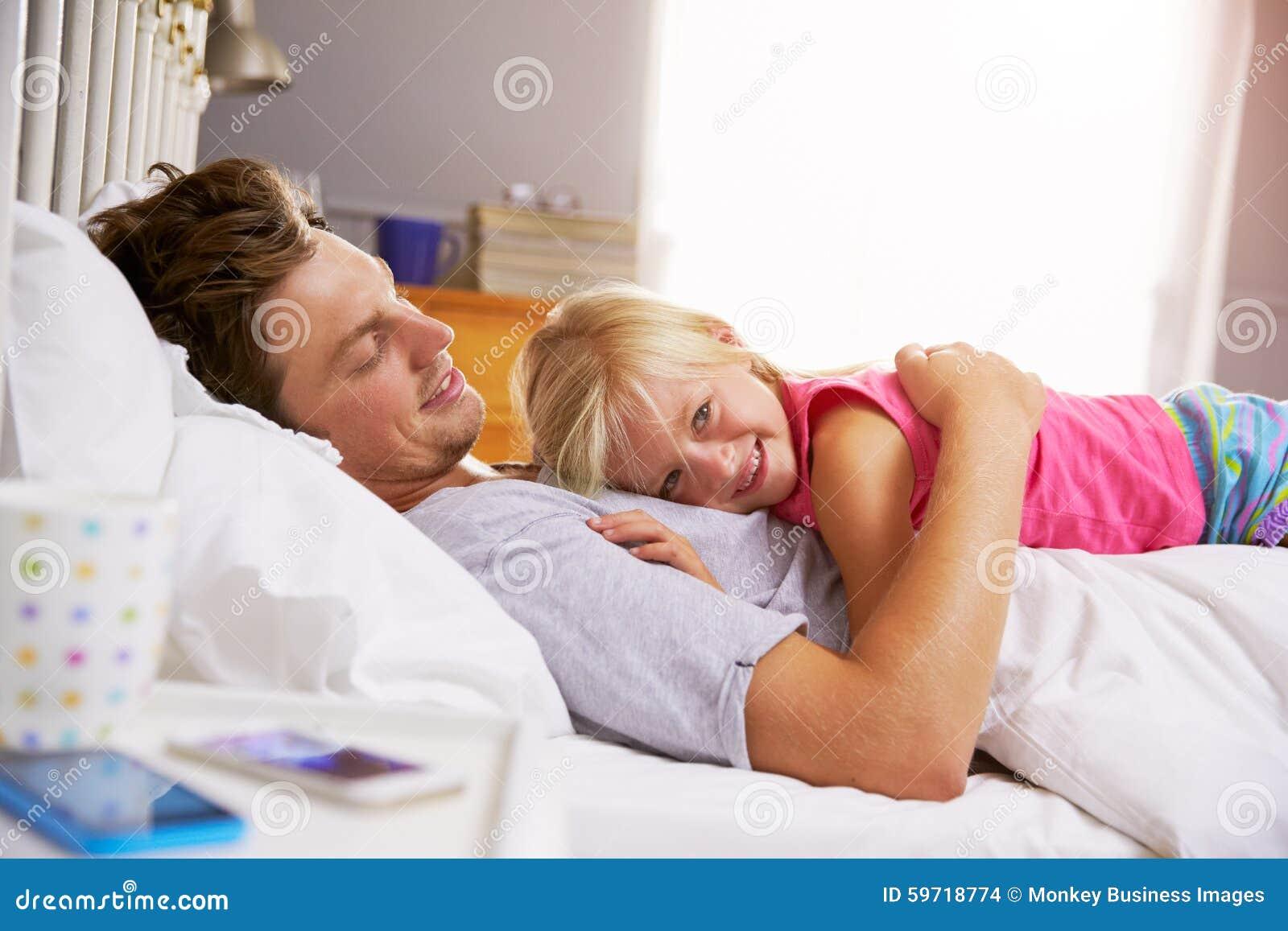 Fader And Daughter Lying i säng tillsammans