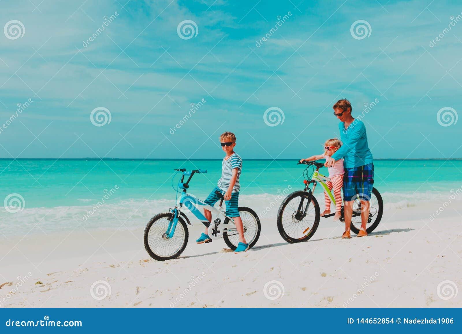 Fader med den lilla sonen och dottern som cyklar p? stranden