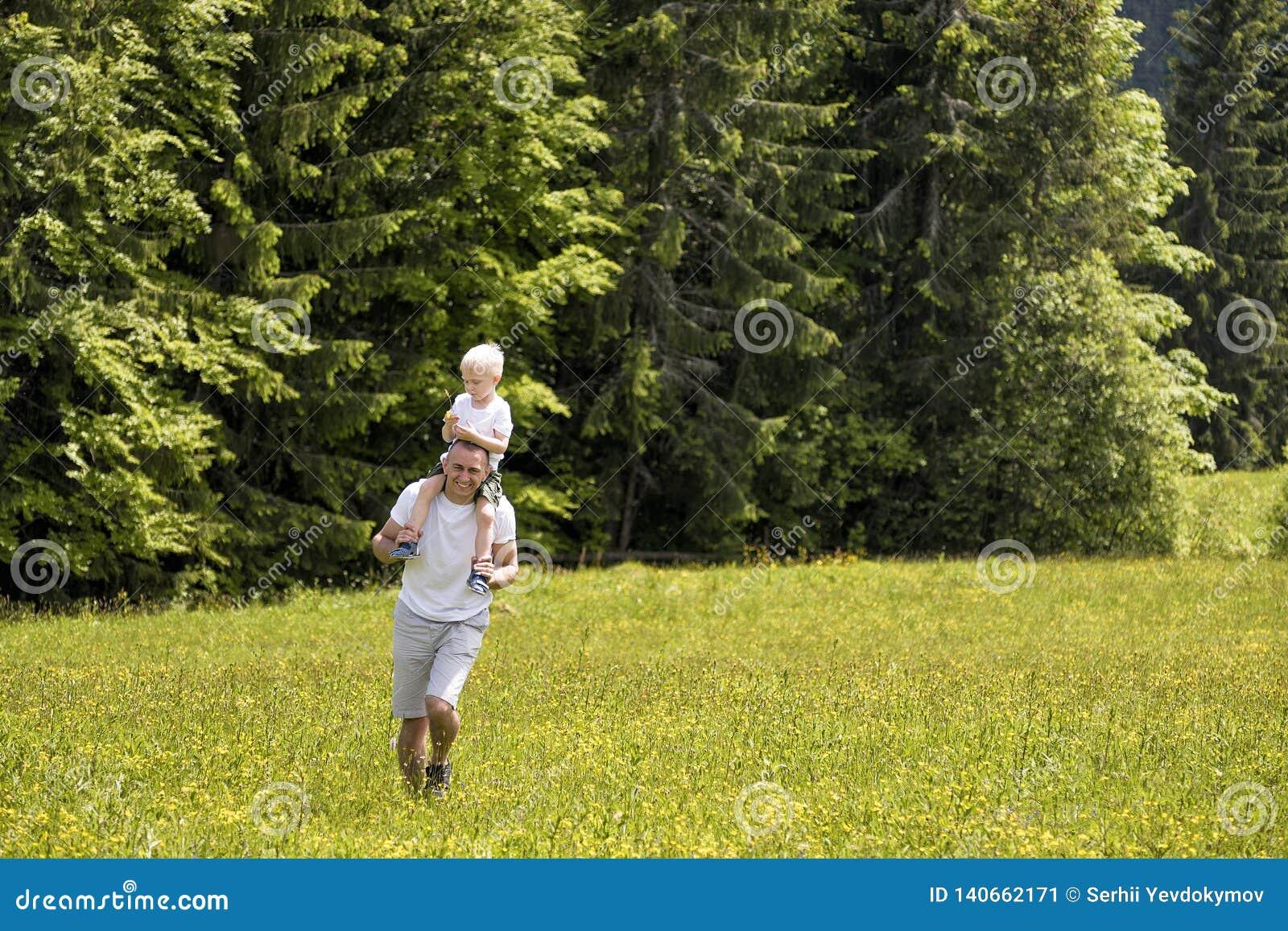 Fader med den lilla sonen på skuldror som går på en grön äng på en bakgrund av gröna pinjeskogar
