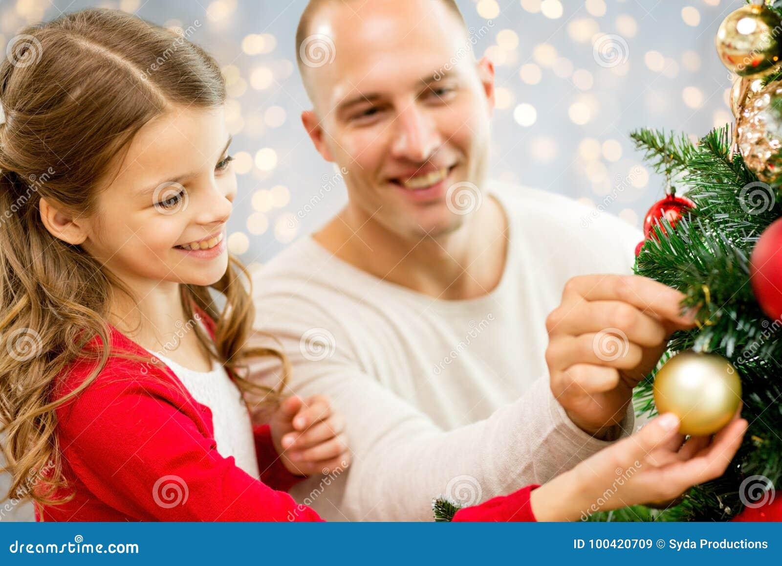 Fader och dotter som dekorerar julträdet