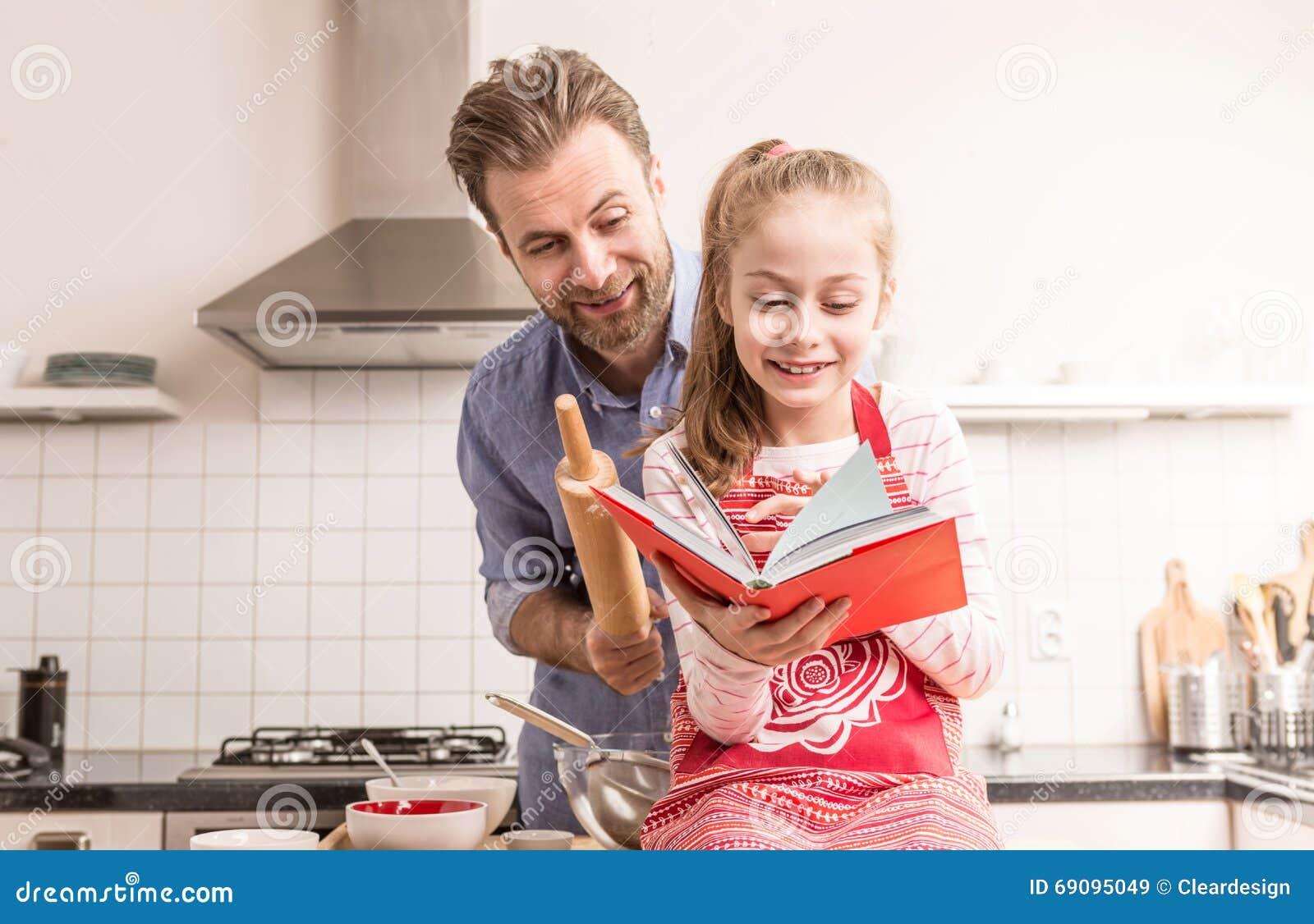 Fader och dotter som har gyckel i köket - baka