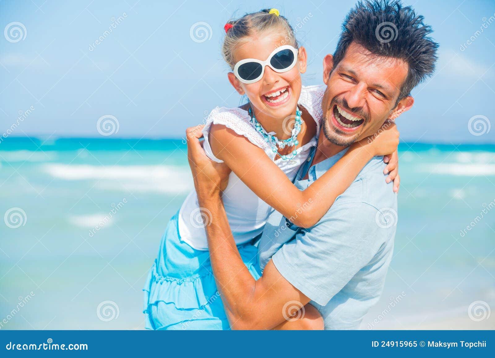 Fader och dotter som har gyckel på strand