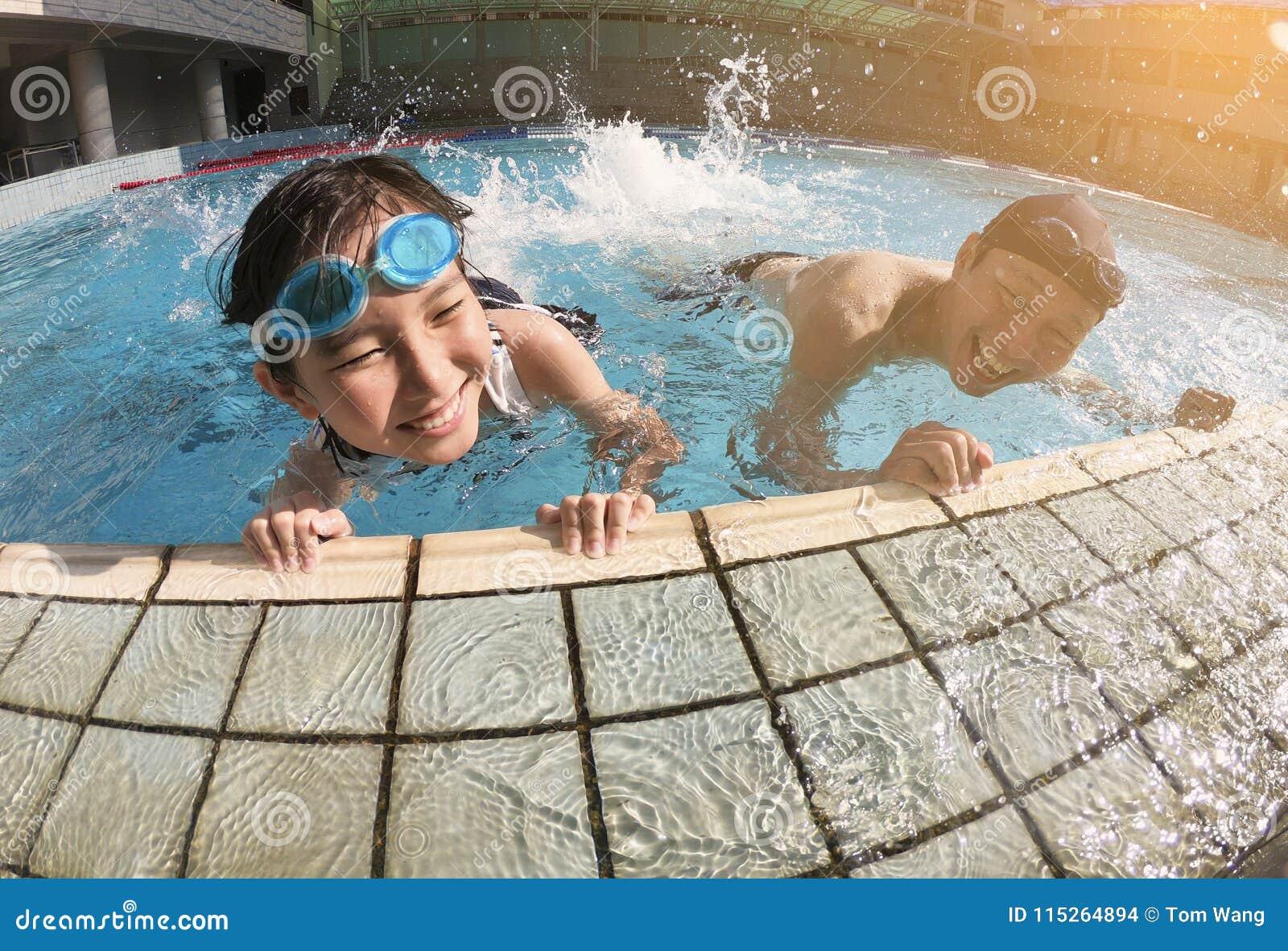 Fader och dotter som spelar i simbassäng