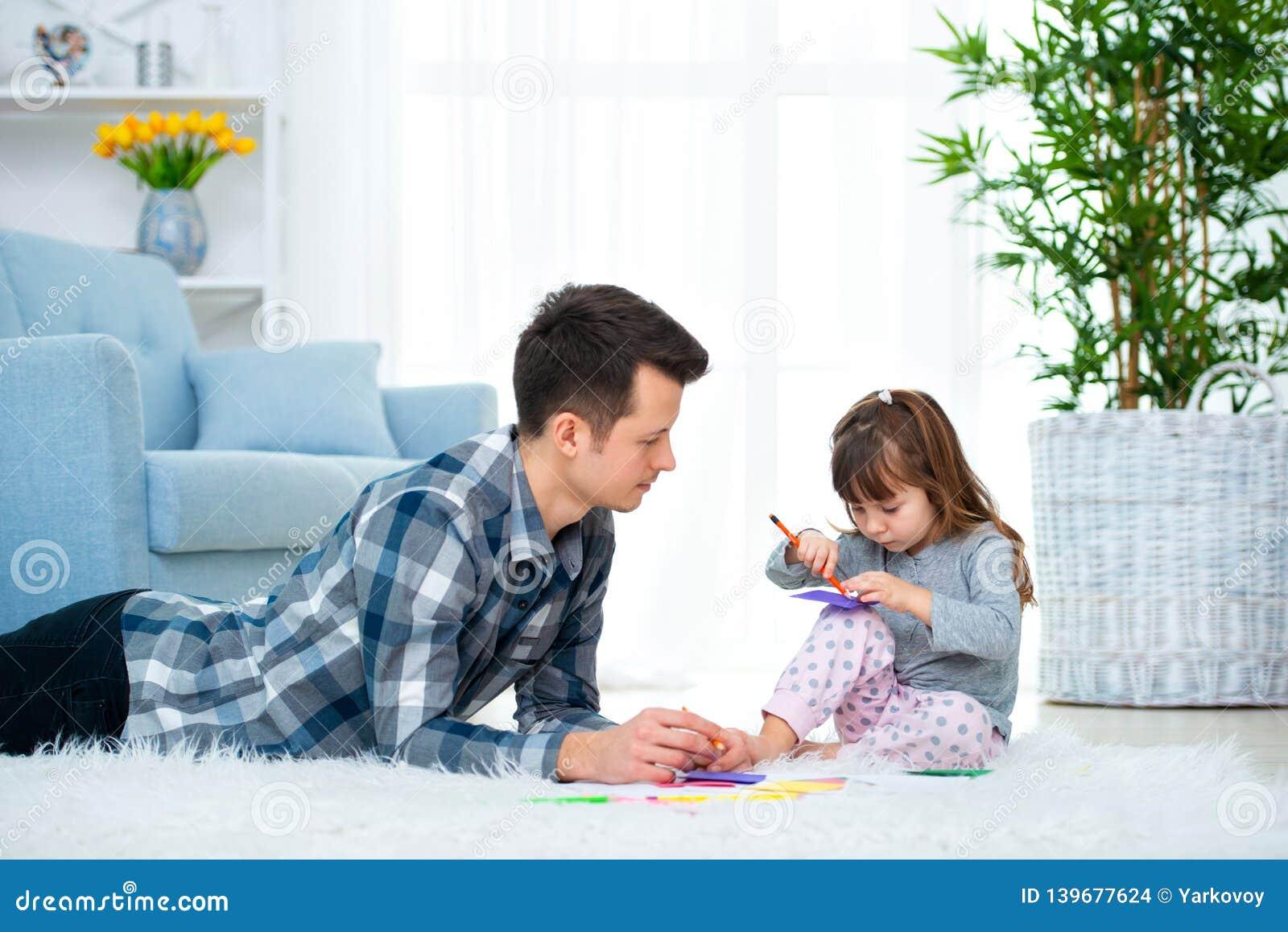 Fader och liten dotter som har kvalitets- familjtid tillsammans hemma farsa med flickan som ligger på varm golvteckning med färgr