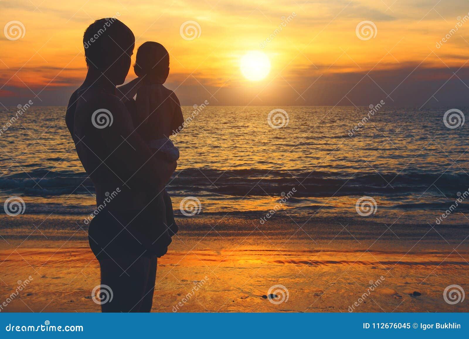 Fader och son på kusten av det azura havet som håller ögonen på för solnedgång Livsstil semester, lycka, glädjebegrepp Fritidsakt