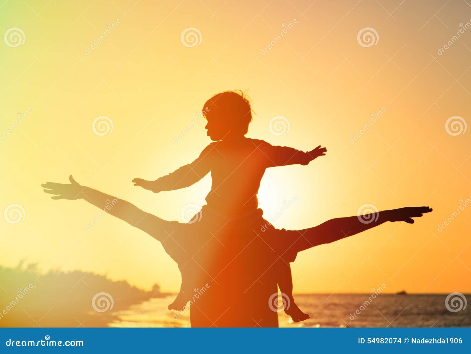 Fader och son som har gyckel på solnedgång
