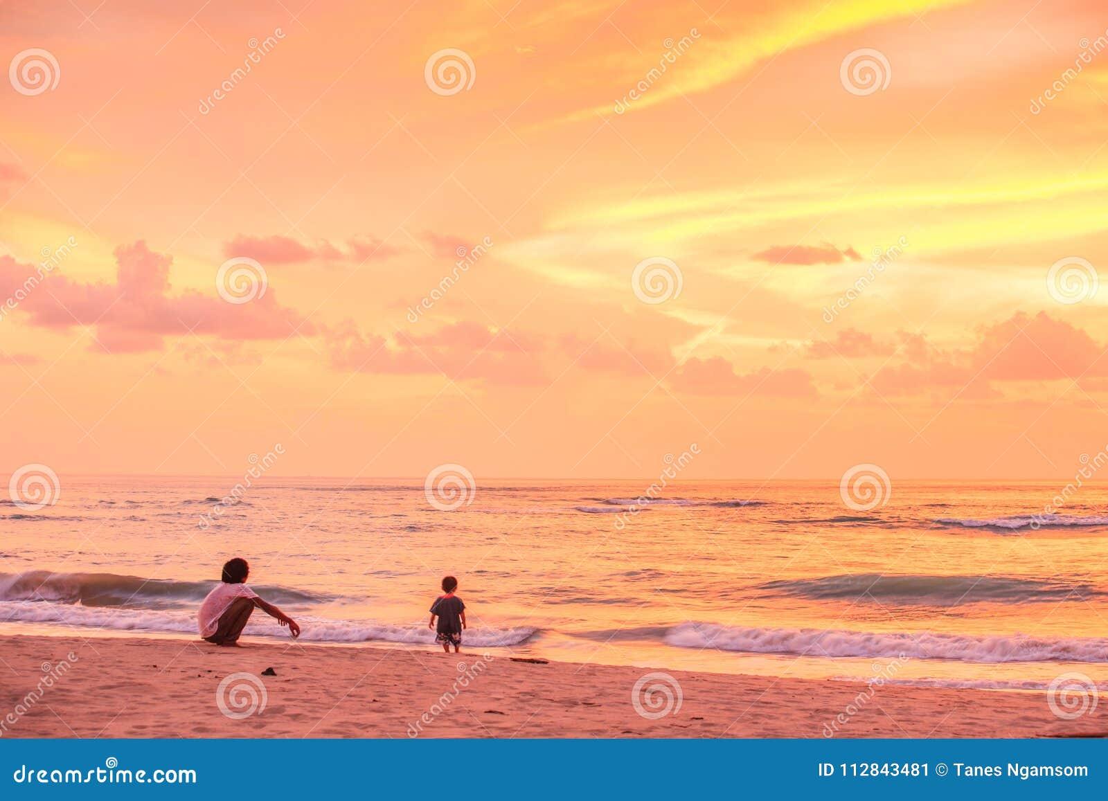 Fader och son som ser solnedgång och fantastisk himmel