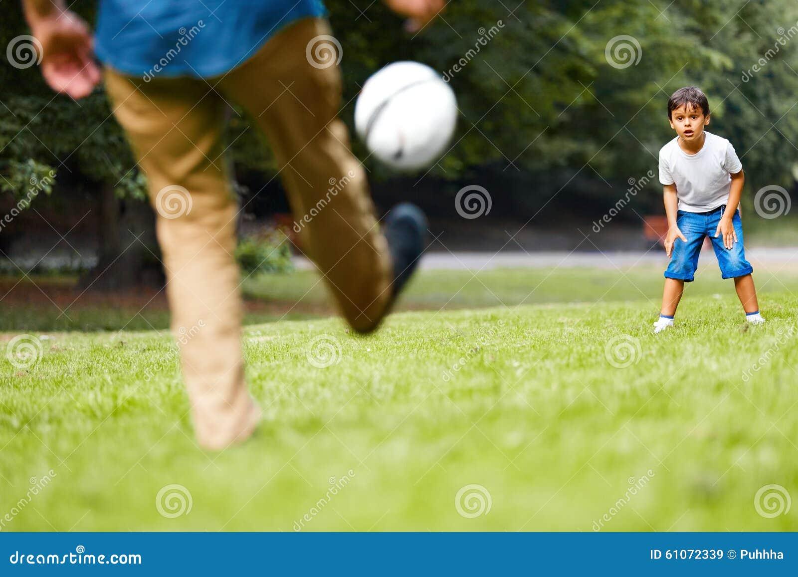 Fader och son som spelar fotboll i parkera