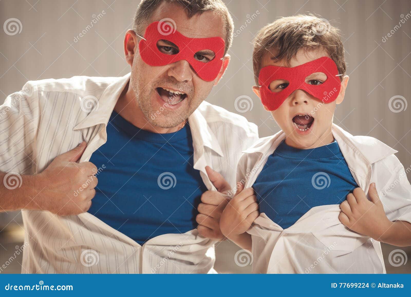 Fader och son som spelar superheroen utomhus på dagtiden