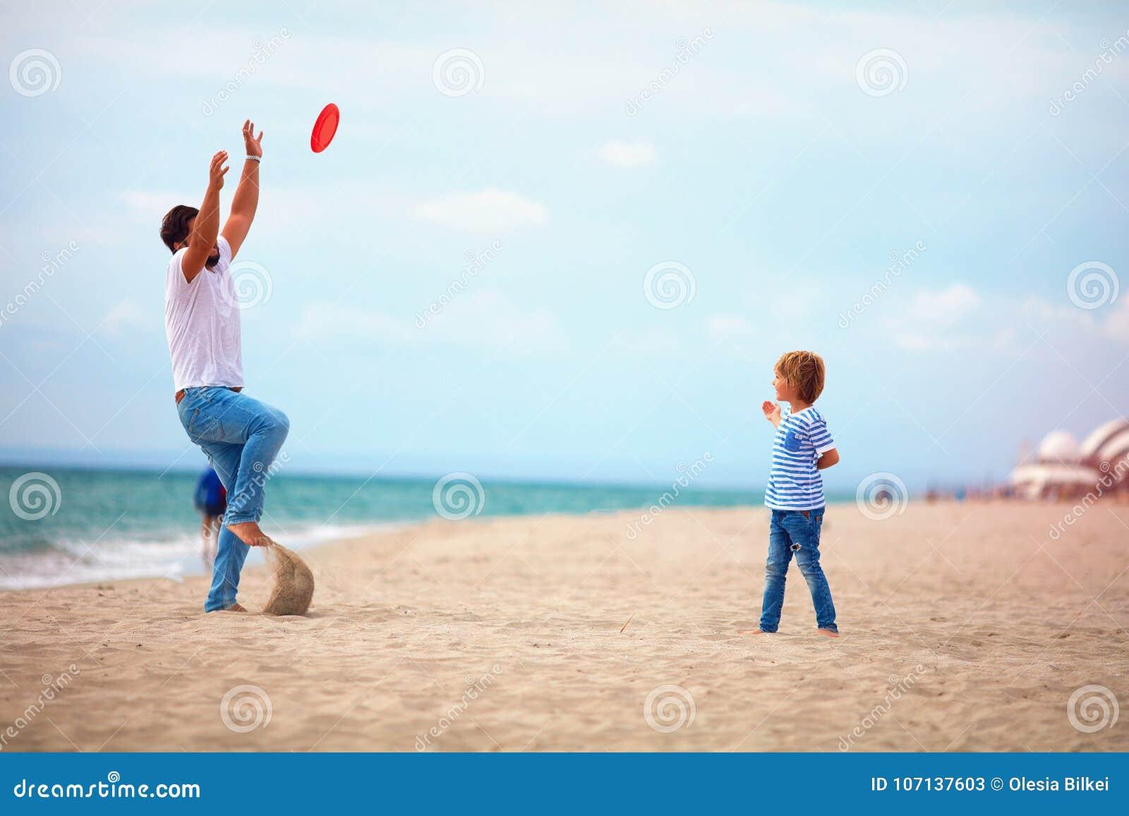 Fader och son som tycker om sommarsemestern som spelar strandaktivitetslekar nära havet, familj som kastar flygskivan