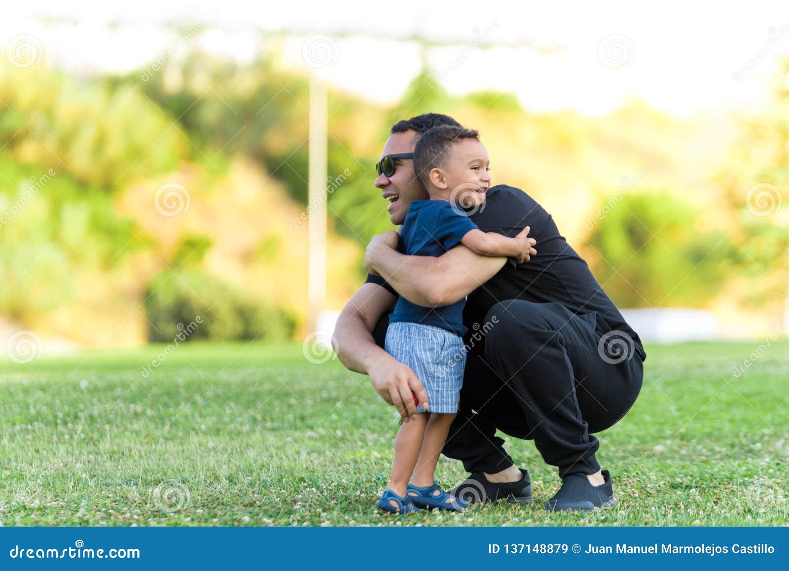 Fader och son som utomhus kramar