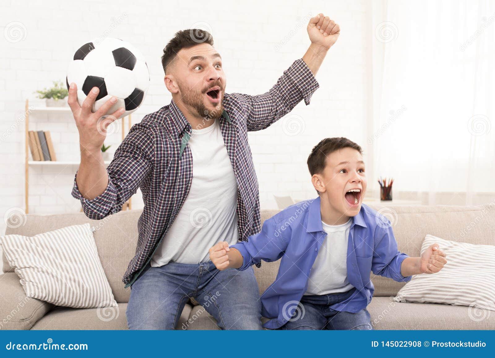 Fader- och sonfotbollfans som hurrar med fotboll, klumpa ihop sig