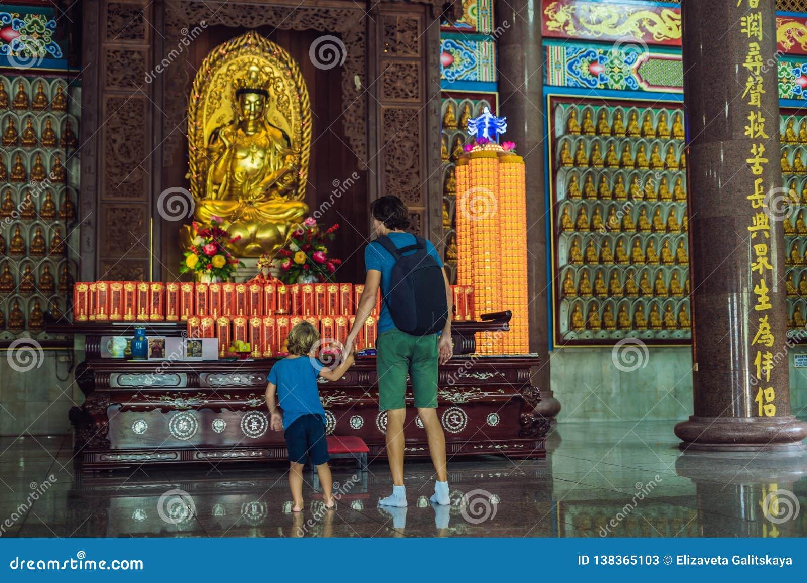 Fader- och sonturister i den buddistiska templet Kek Lok Si i Penang, Malaysia, Georgetown Resa med barnbegrepp