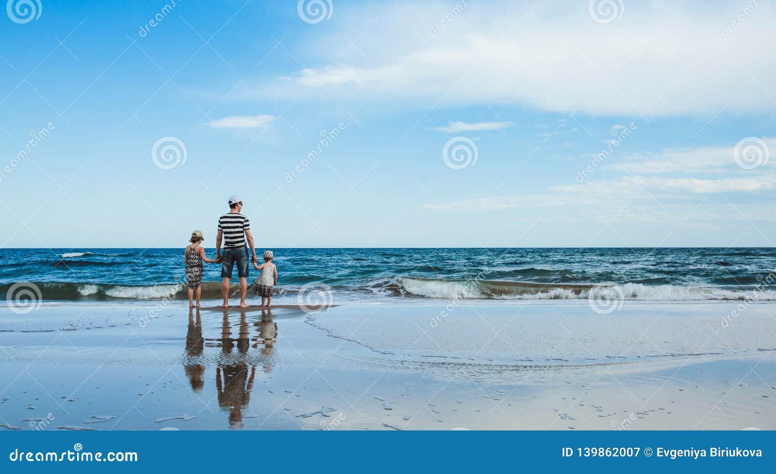 Fader och två döttrar som står på stranden