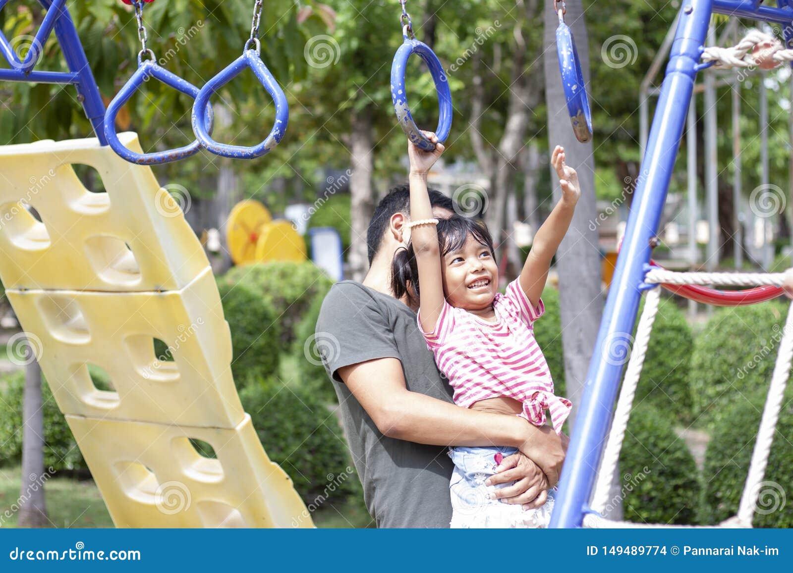 Fader som rymmer en dotter som spelar p? lekplatsen p? ferie