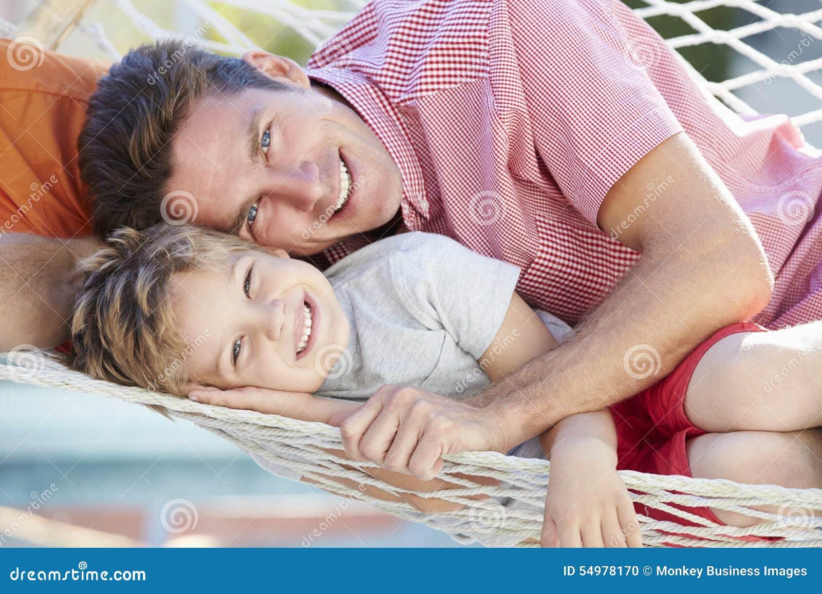 Fader And Son Relaxing i trädgårds- hängmatta tillsammans
