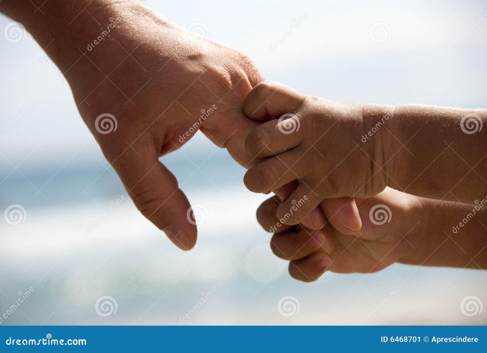 Fadern hands holdingsonen