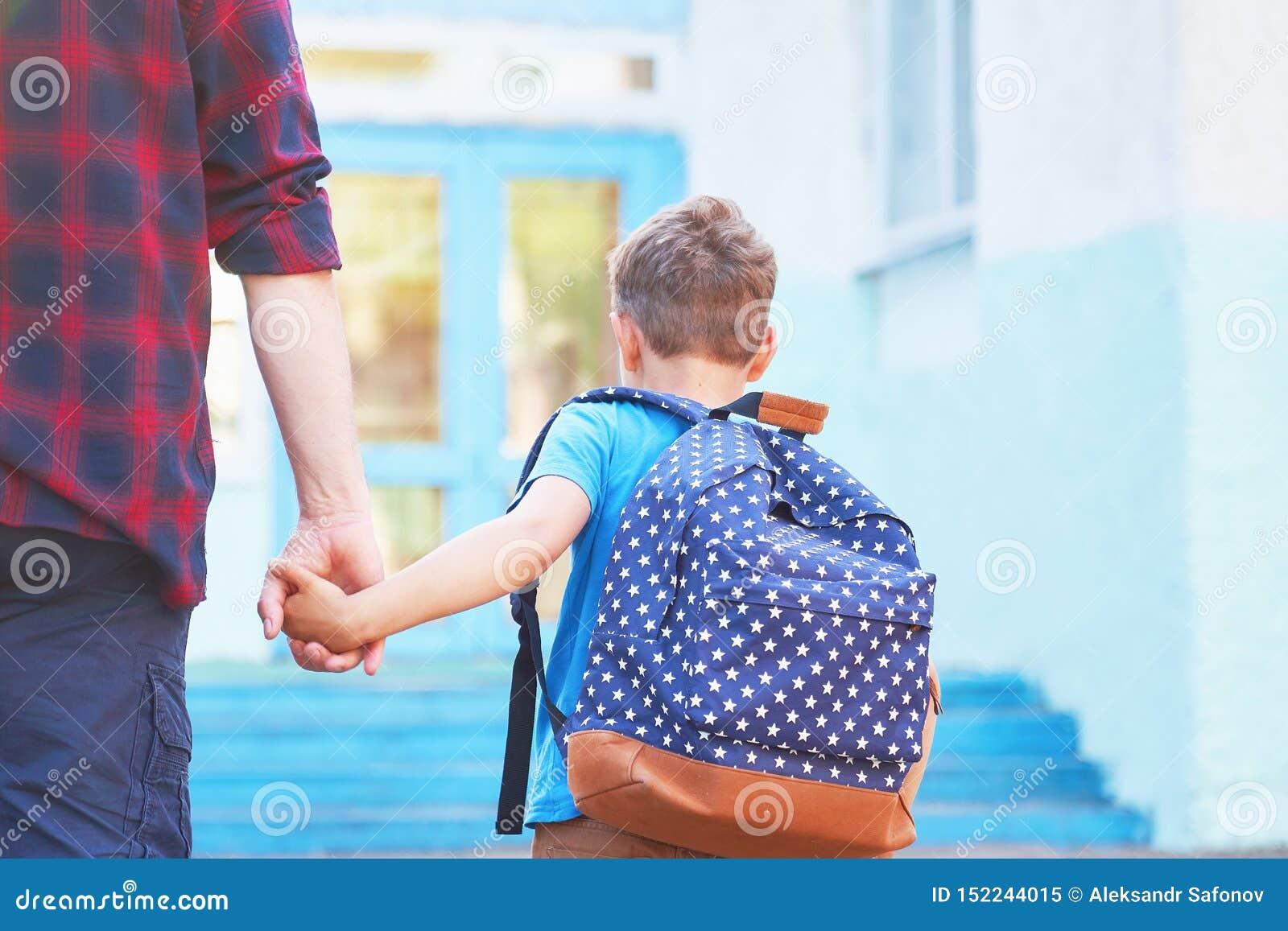 Fadern medföljer barnet till skola en man med ett barn som tas bort från baksidan doting farsa som rymmer handen av hennes son so