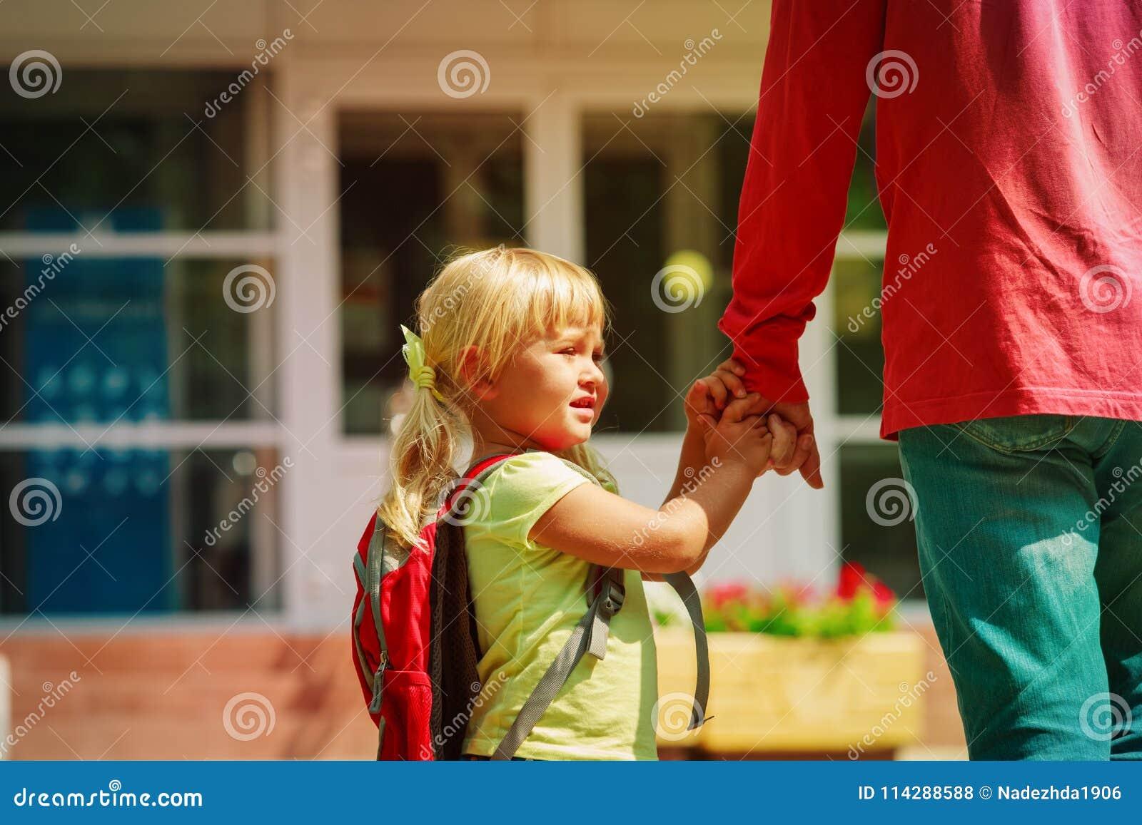 Fadern och den lilla dottern går till skolan eller daycare