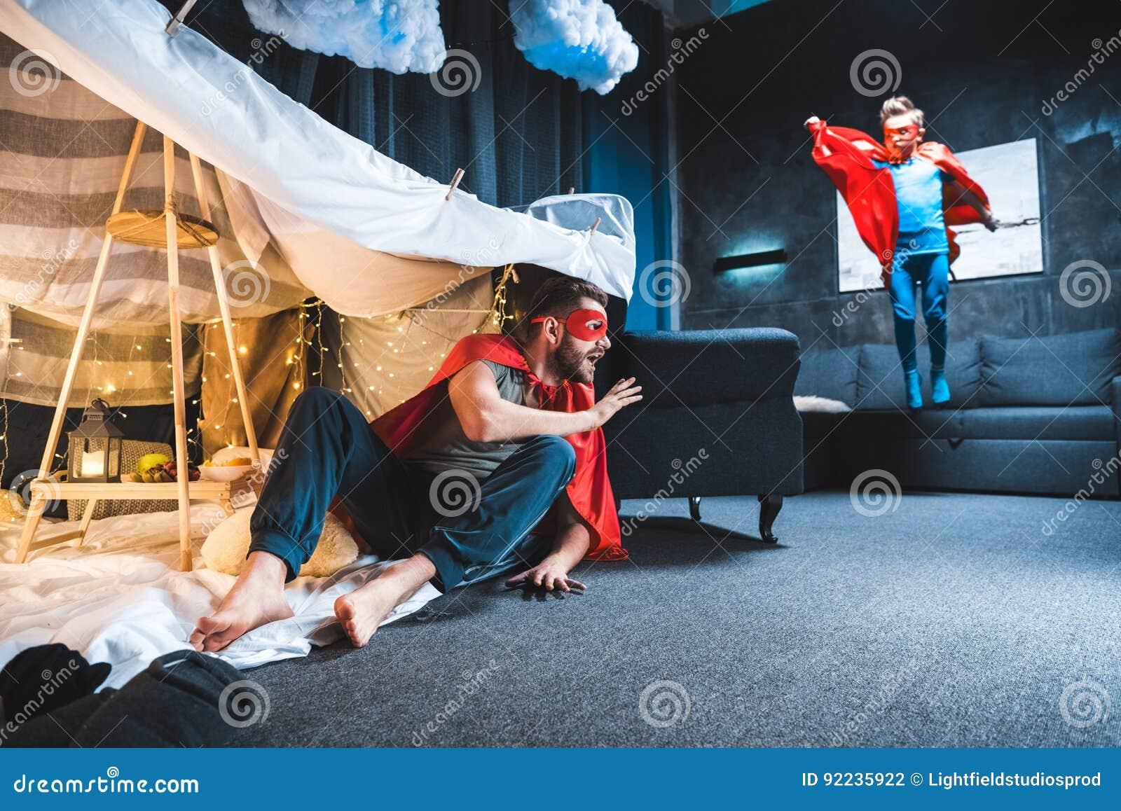 Fadern och sonen i röd superhero kostymerar att spela