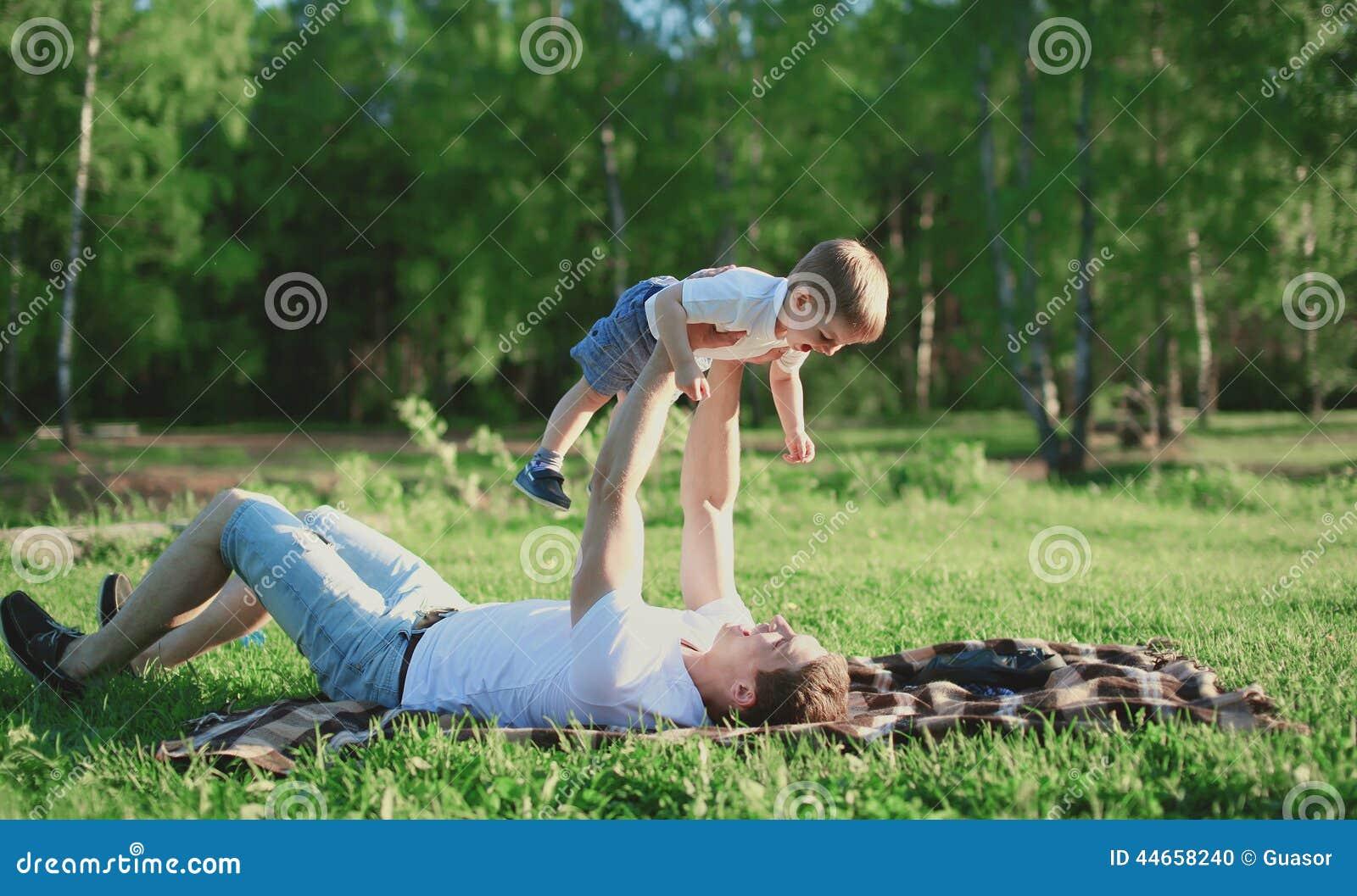 Fadern och sonen vilar i parkera och att ha gyckel, familj