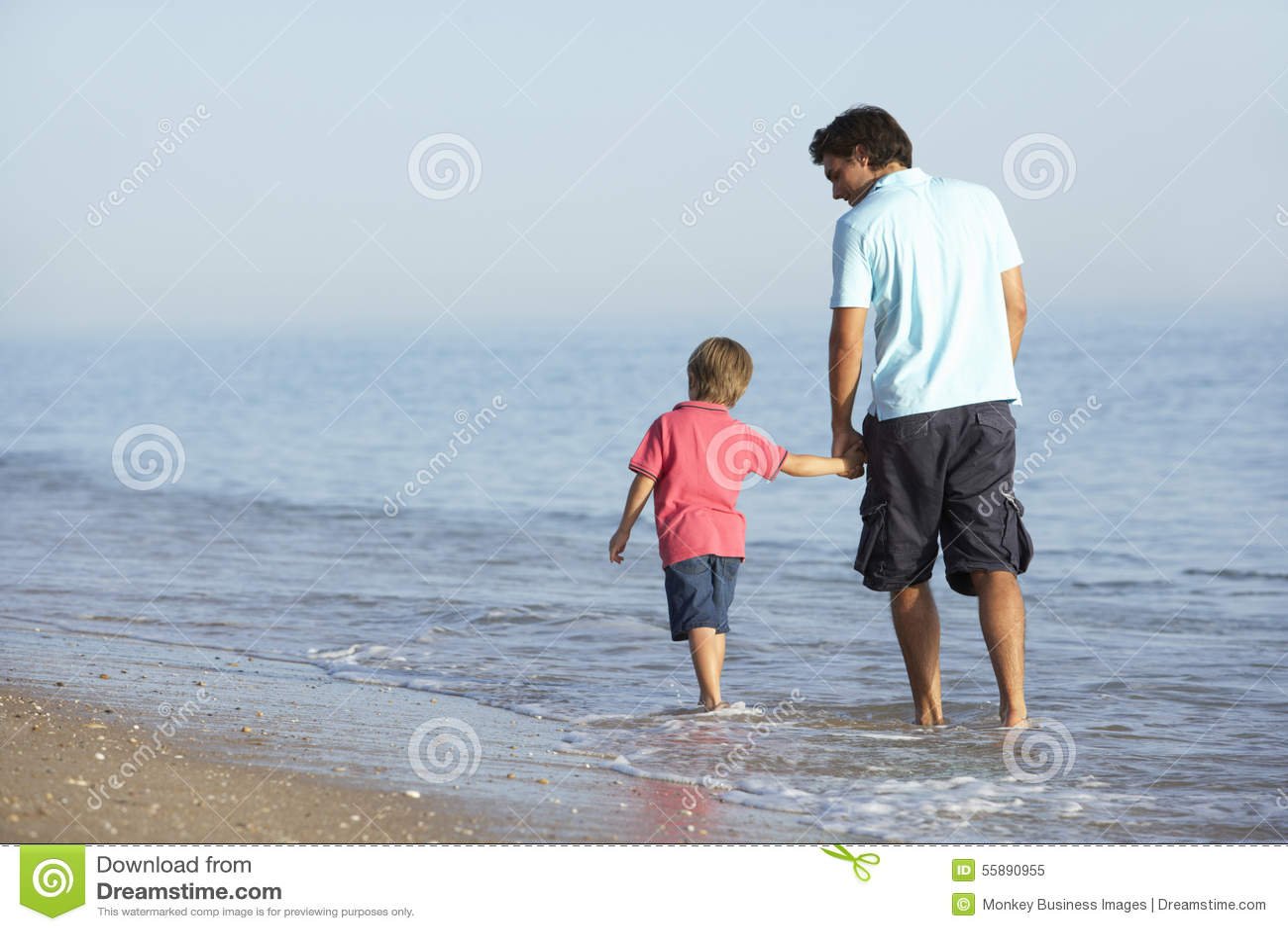 Fadern And Son Enjoying promenerar stranden