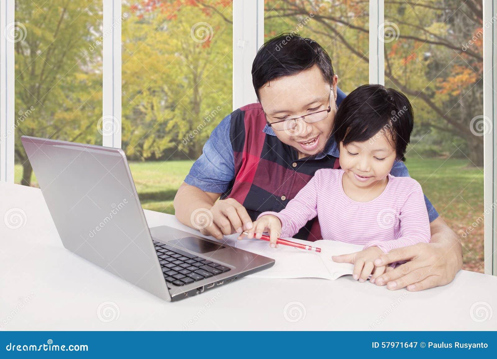 Fadern undervisar hans barn som gör läxa med boken