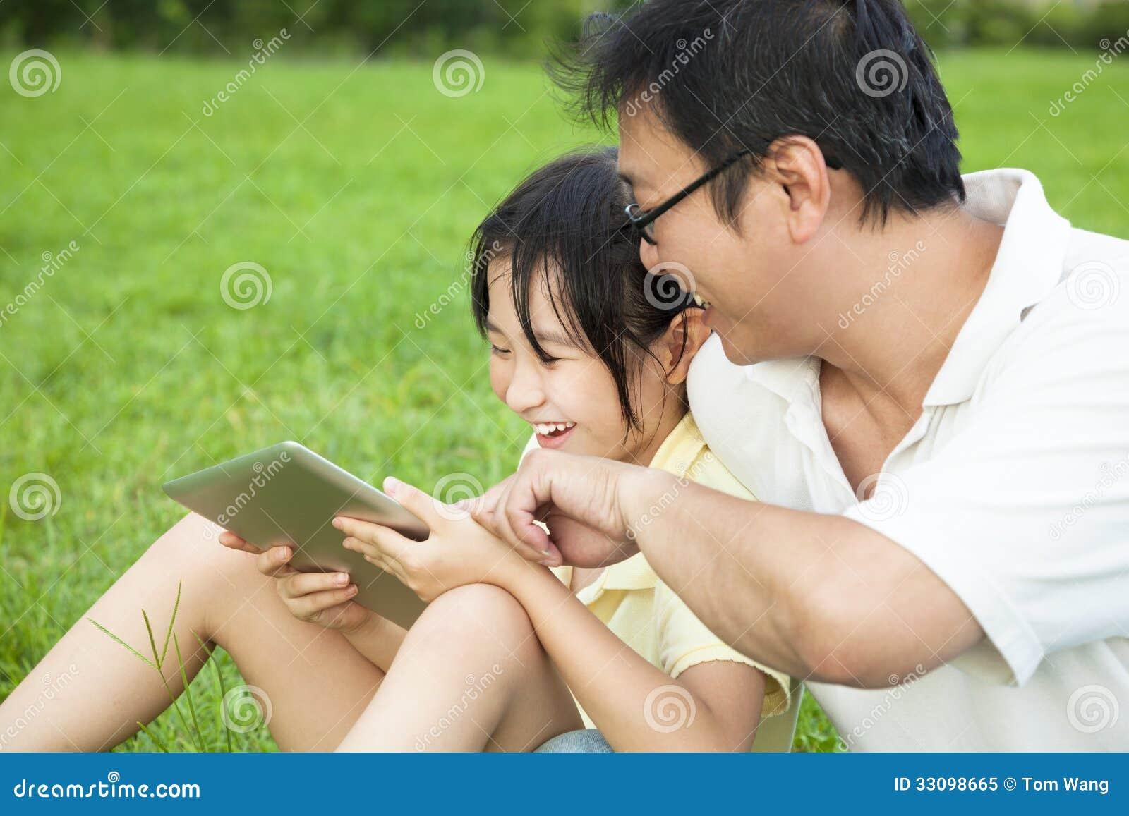 Faderundervisningliten flicka som använder minnestavlaPC