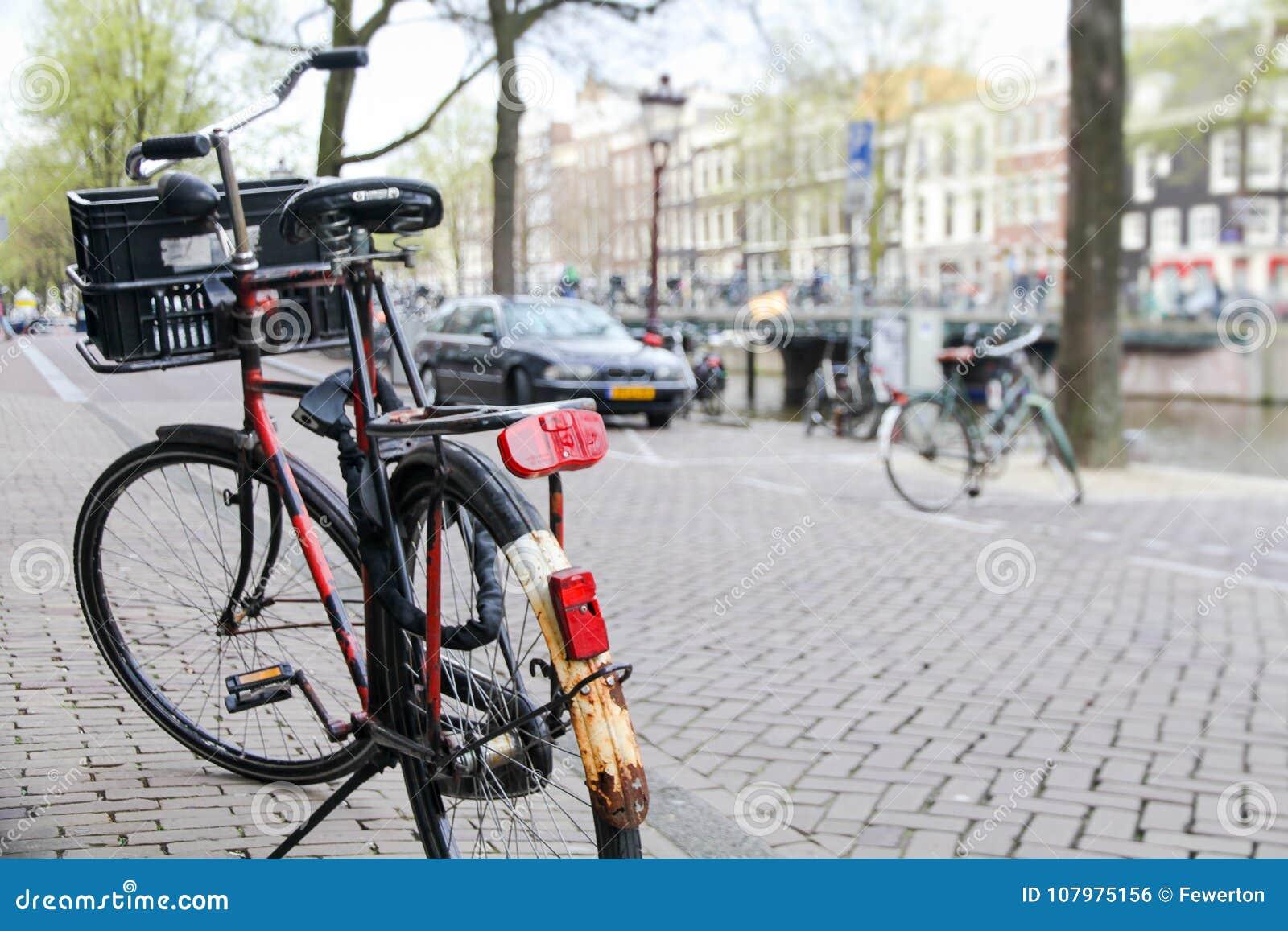 Fahrrad parkte auf der Straße im Vordergrund mit einem typischen Kanal und einer Architektur von Amsterdam, die Niederlande