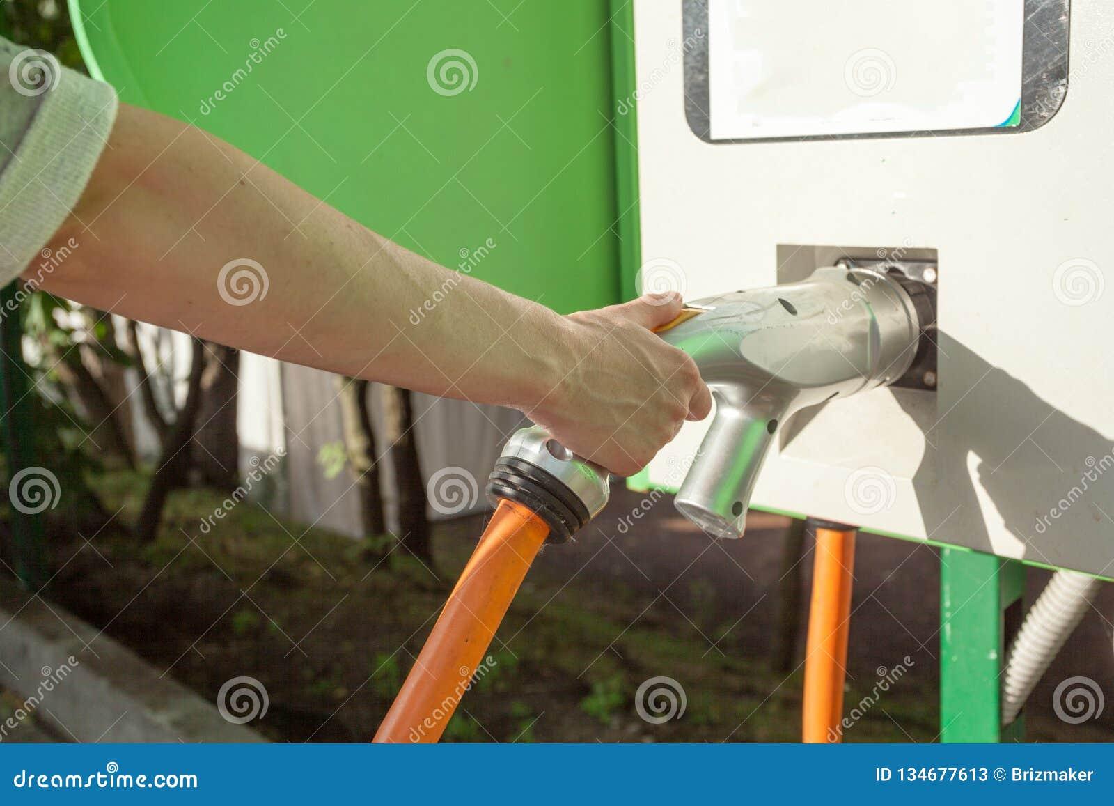 FAHRZEUG-Energieenergie des Elektroautos Aufladungsfür umweltfreundliches Frau, die Aufladungskabel des Elektroautos hält