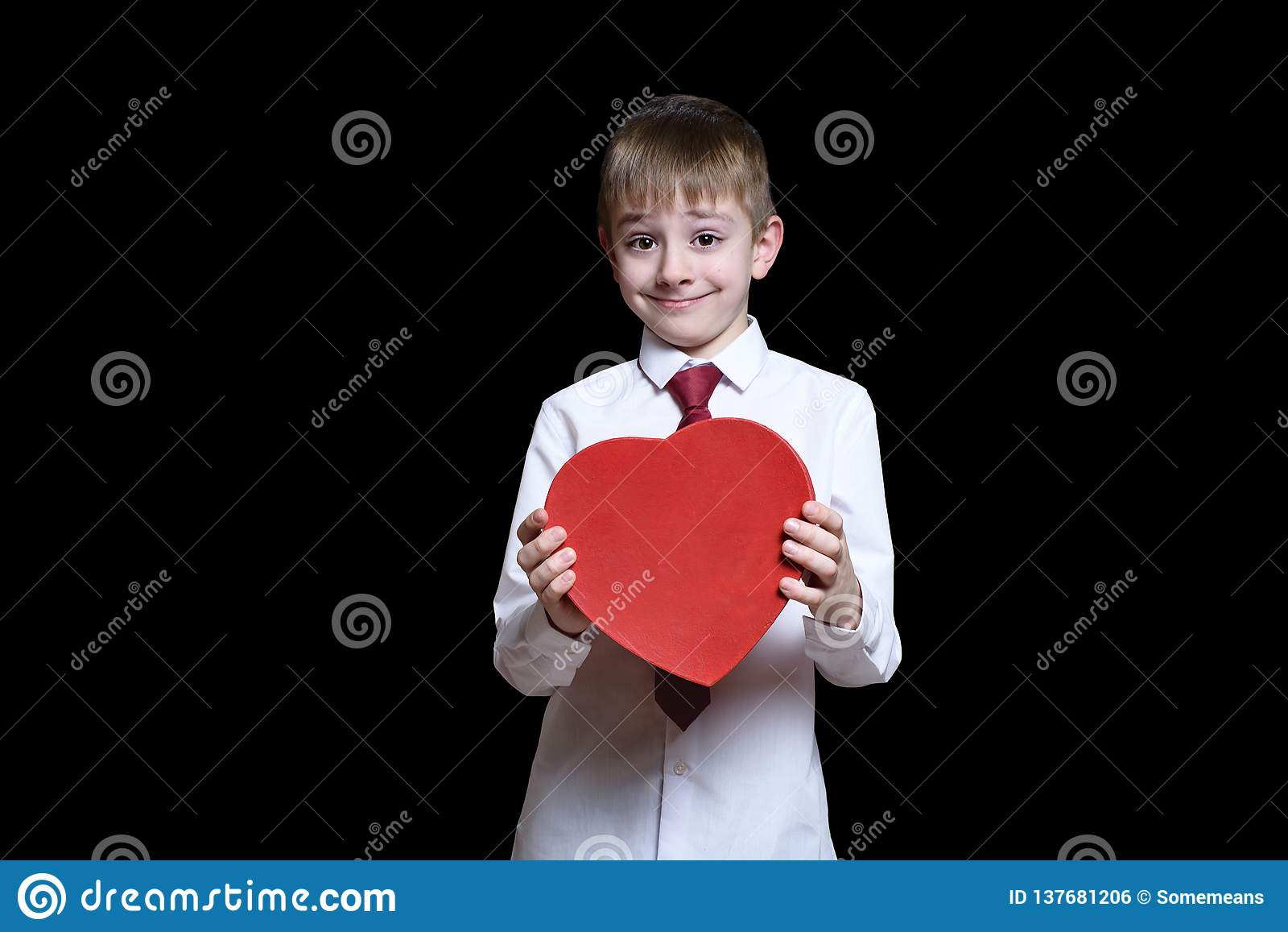 1d08f4235d8b Fair-haired boy in a shirt and tie holding a red heart shaped box. Love and  family concept. Isolate on black background.