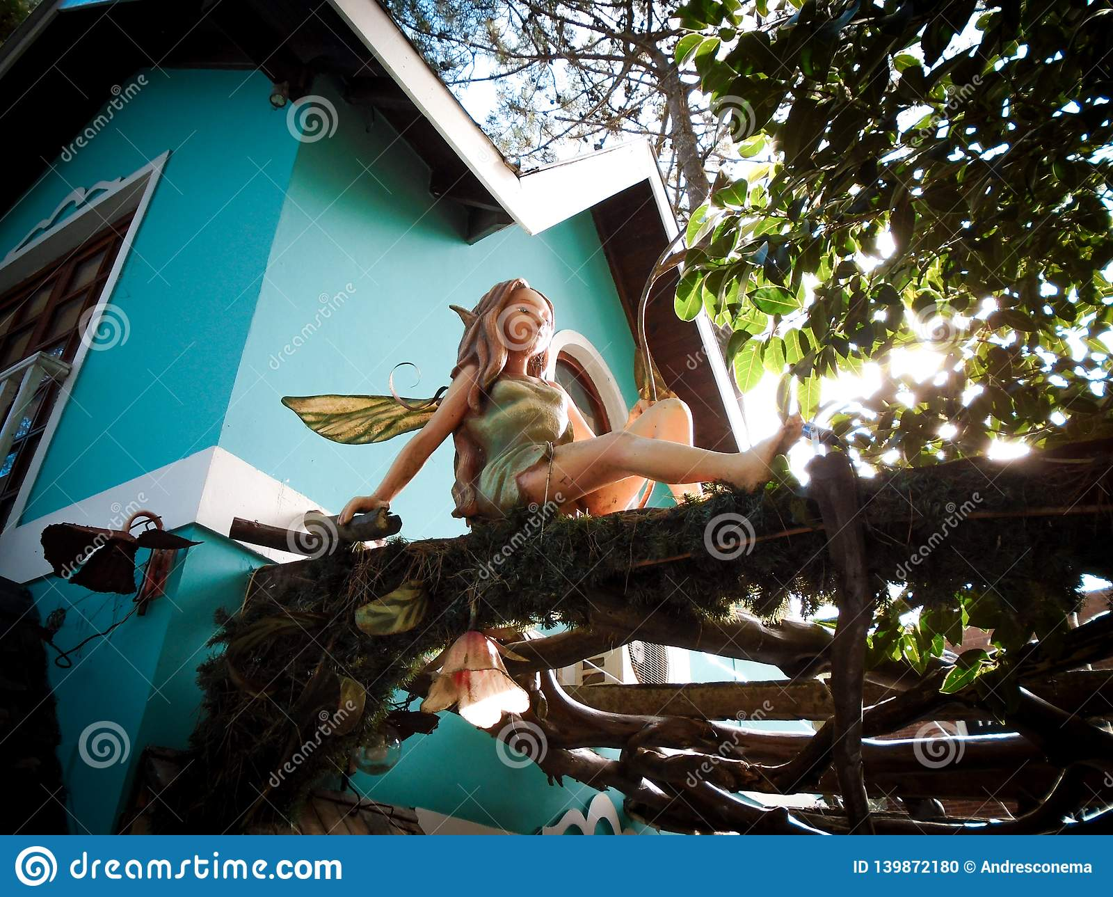 Fairy with dragonfly wings sitting at a wooden pergola