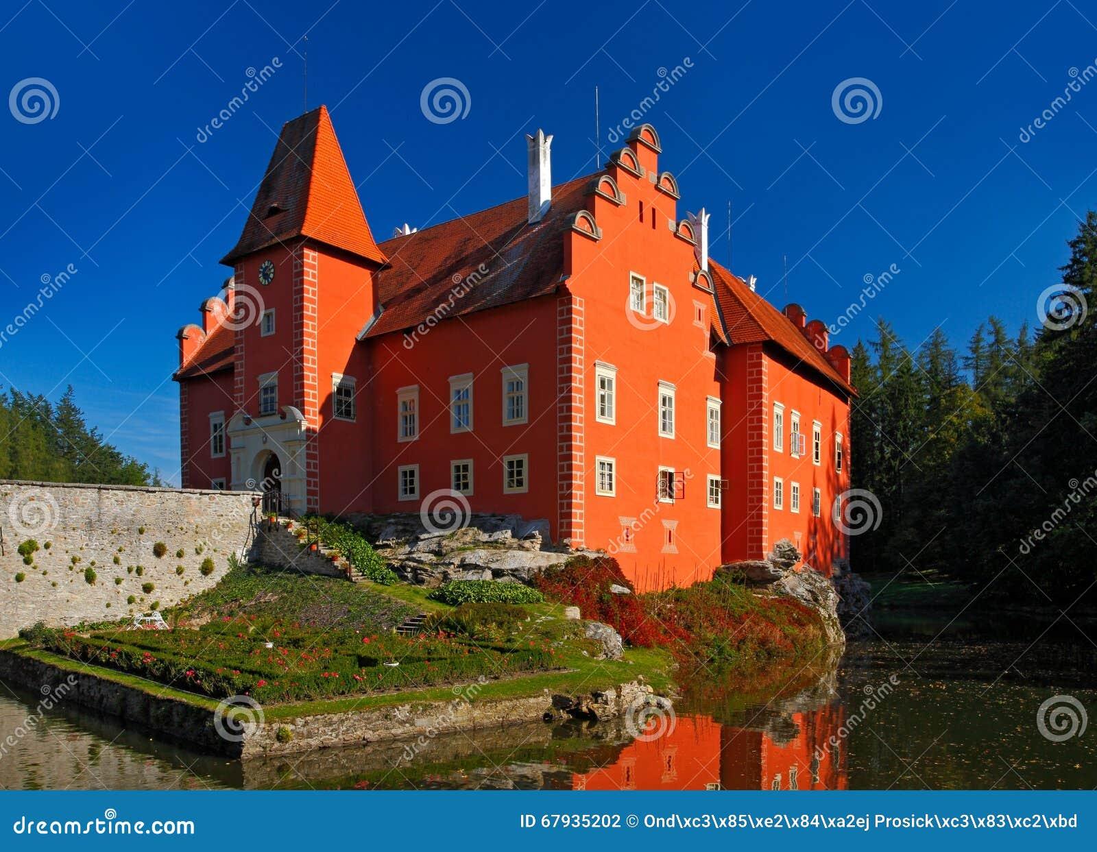Fairy tale red castle on the lake, with dark blue sky, state castle Cervena Lhota, Czech republic
