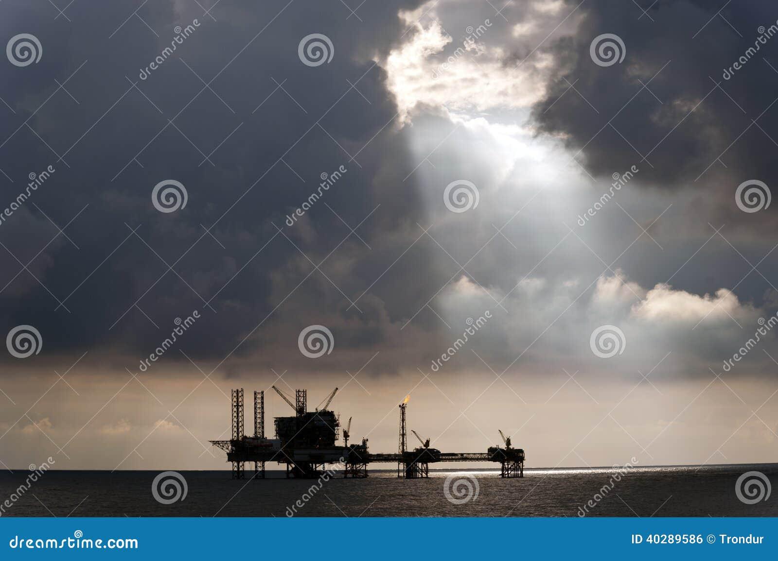 Faisceaux lumineux de Sun au-dessus de plateforme pétrolière