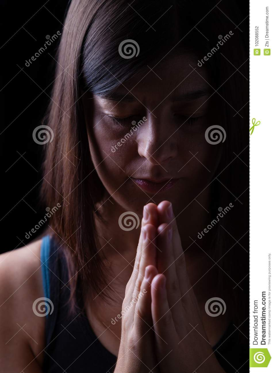 Faithful athletic woman praying, with hands folded in worship to god