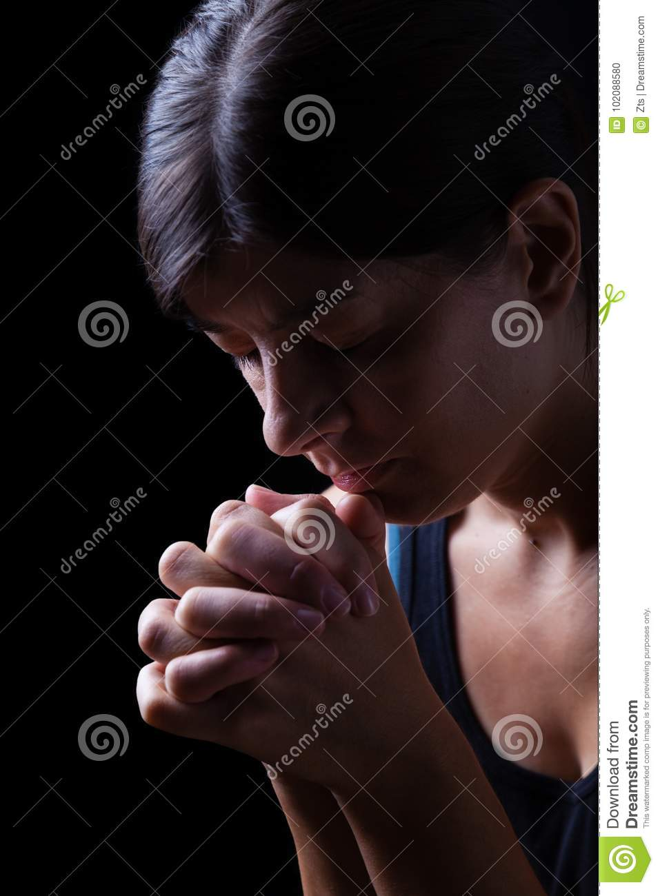 Faithful woman praying, hands folded in worship to god
