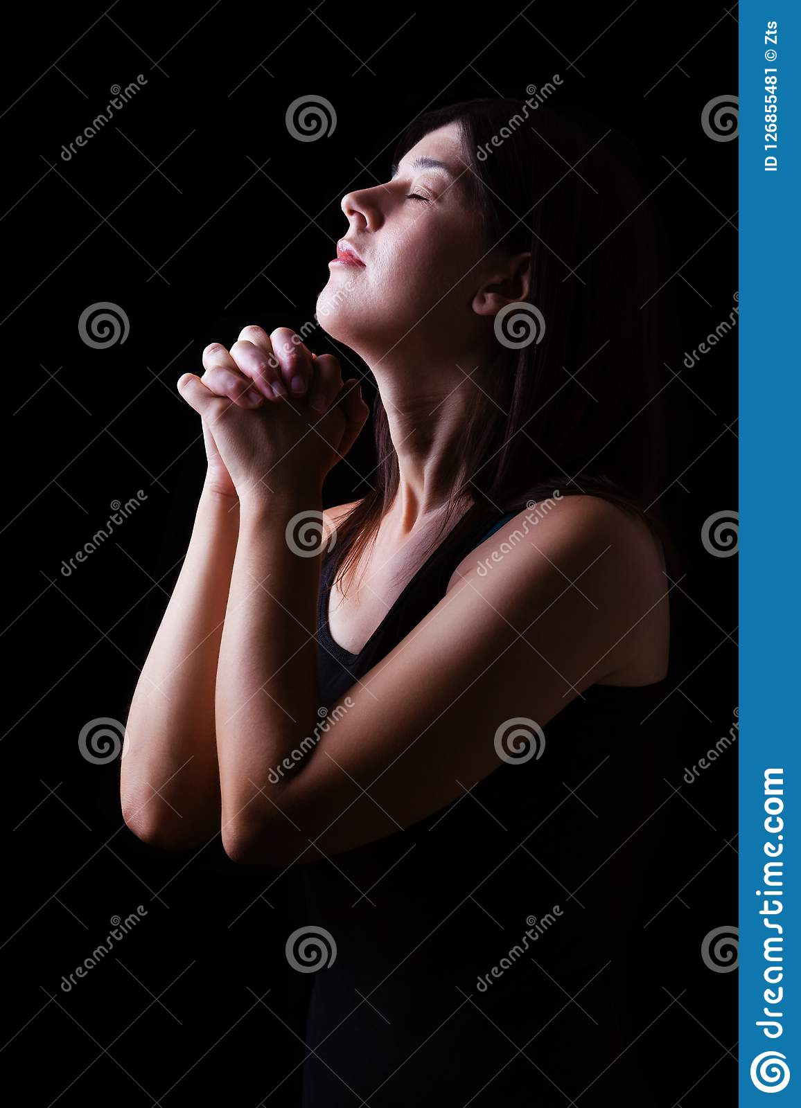 Faithful woman praying, hands folded in worship to god with head up and closed eyes