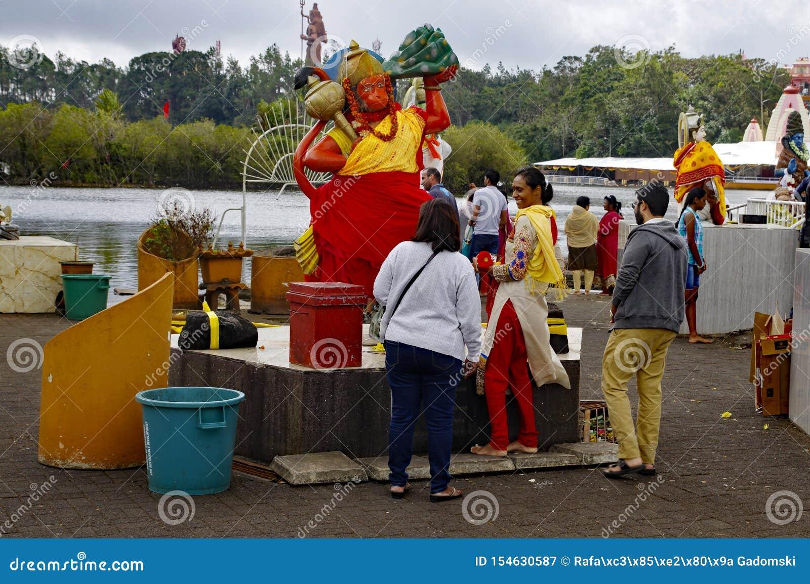 Faithul perto da estátua de Hanuman God no templo hindu e no Ganga Talao Lago crater em Bassin grande Ele