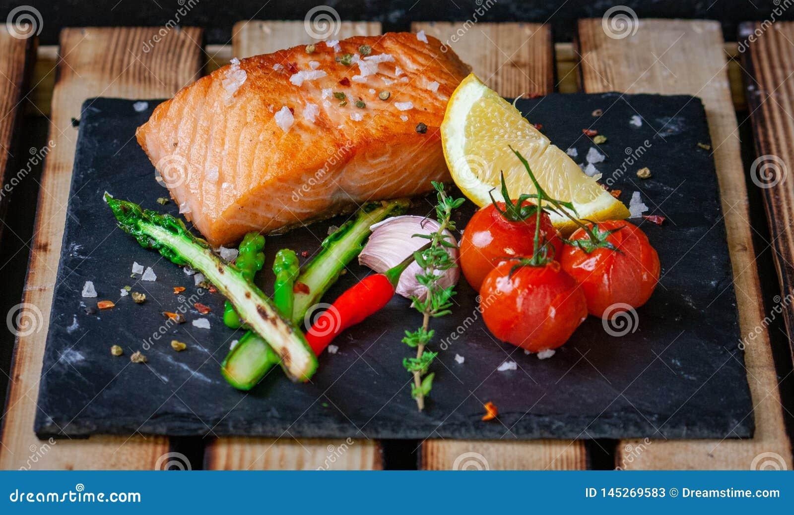 Faixa grelhada deliciosa dos salmões com aspargo verde,