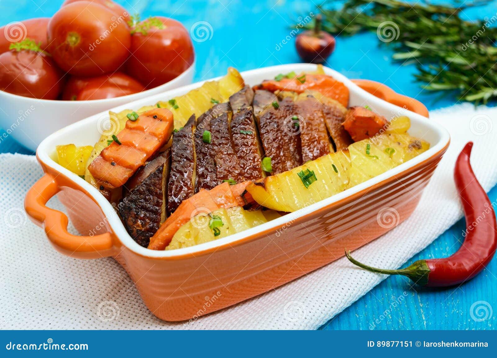 Faixa Roasted do ganso da carne do peito, cortada, das batatas rústicas em uma bacia cerâmica