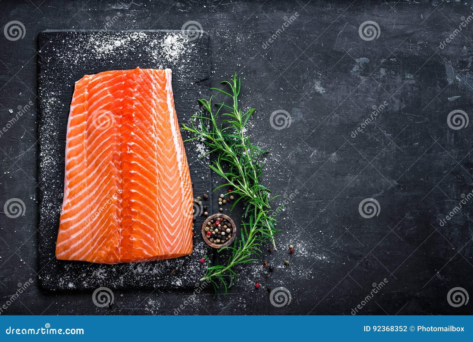 Faixa salmon crua no fundo escuro da ardósia, peixe atlântico selvagem, espaço para o texto