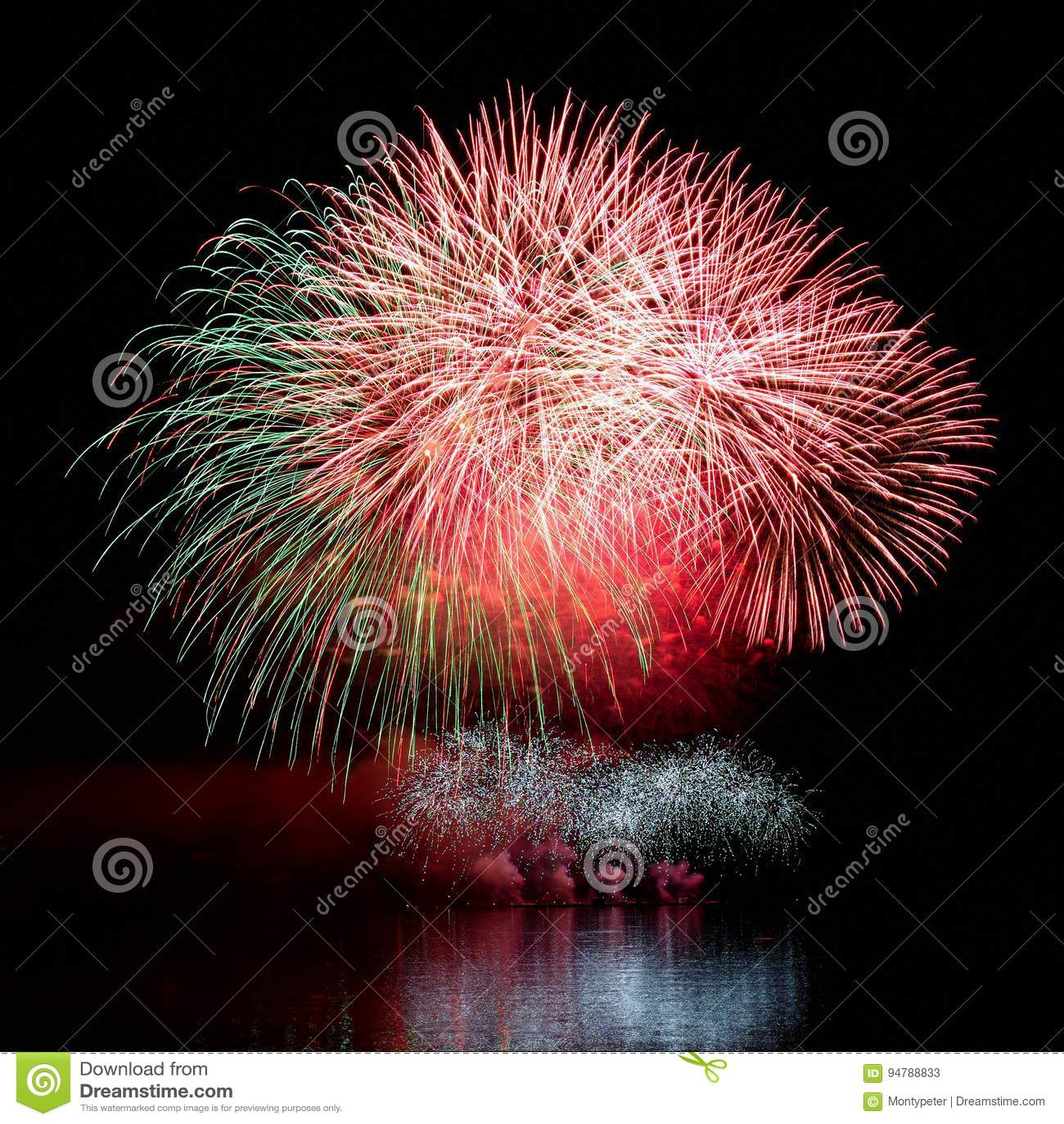 Fajerwerk Piękni kolorowi fajerwerki na nawadniają powierzchnię z czystym czarnym tłem Zabawa festiwal i konkurs strażak