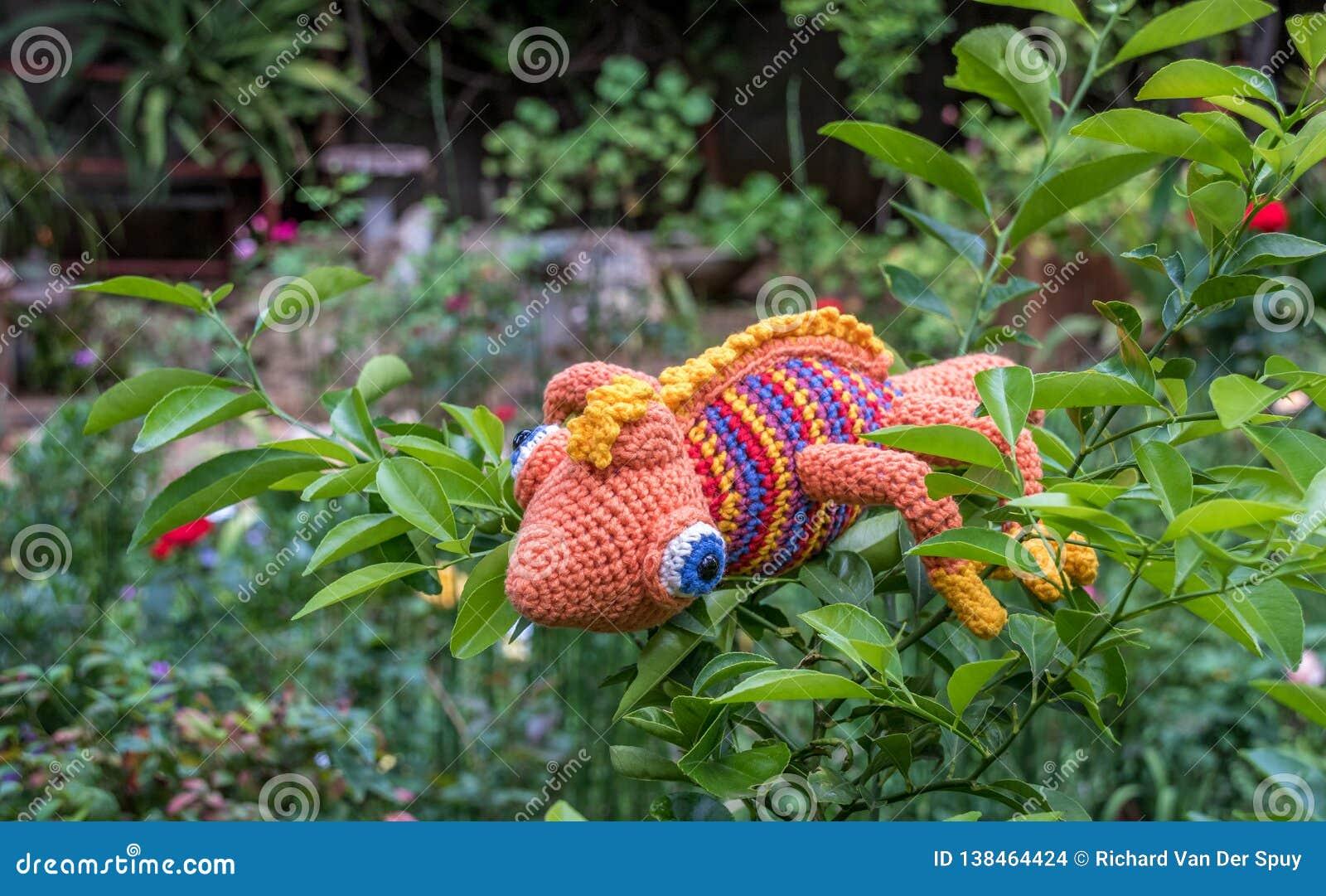 Fake chameleon on a green bush