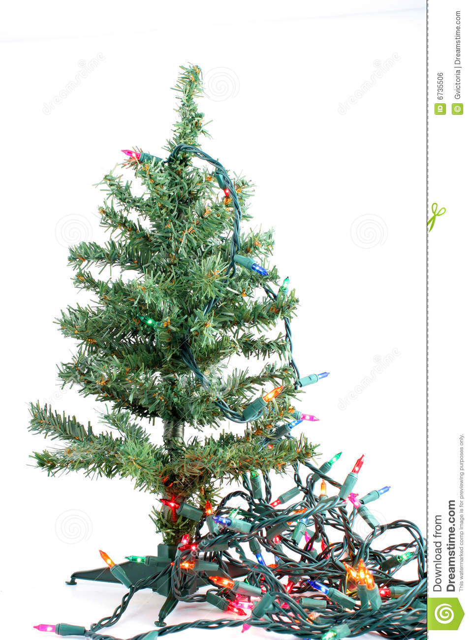 small fake green christmas tree waiting to be decorated on a white background with colorful christmas lights hanging