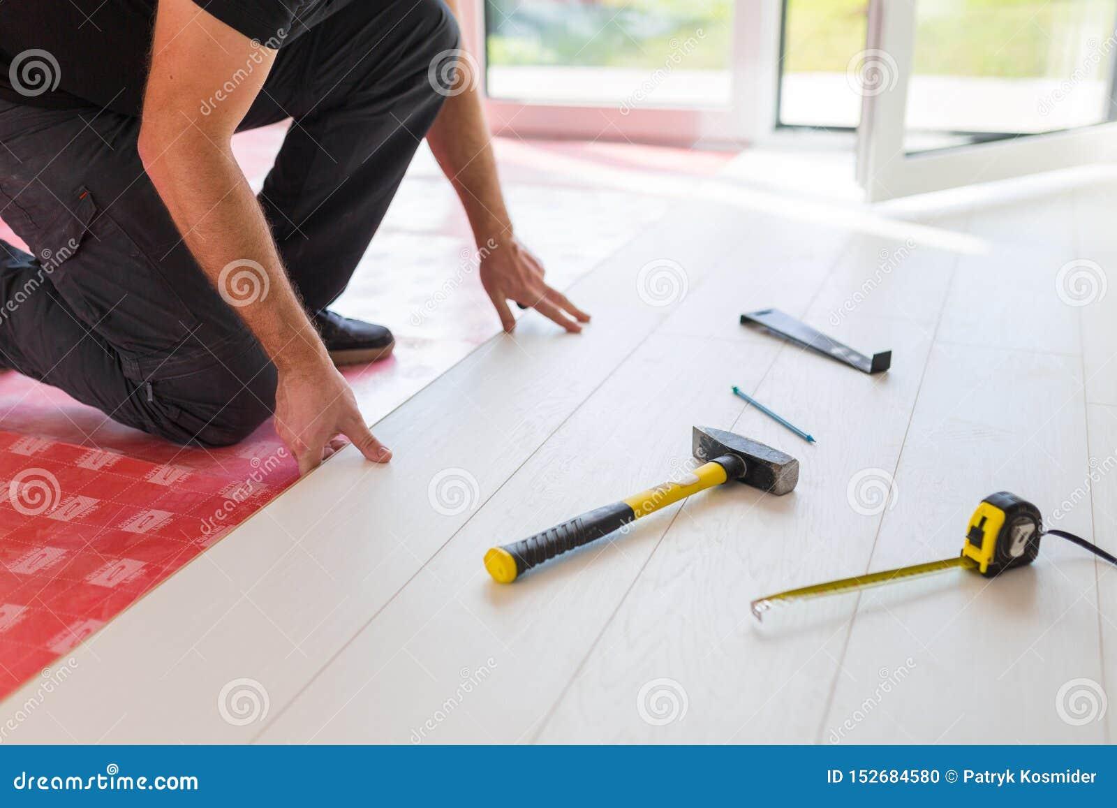 Faktotum som installerar det nya pl?terade tr?golvet