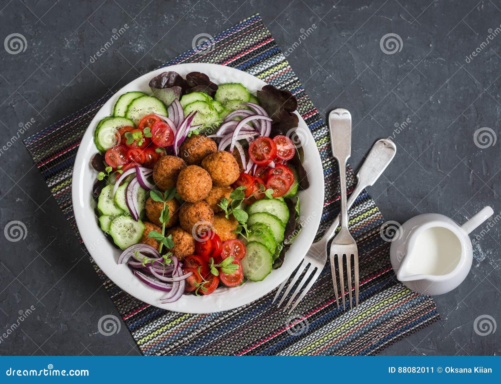 Falafel i świezi warzywa sałatkowi na ciemnym tle, odgórny widok Jarosz, diety jedzenie