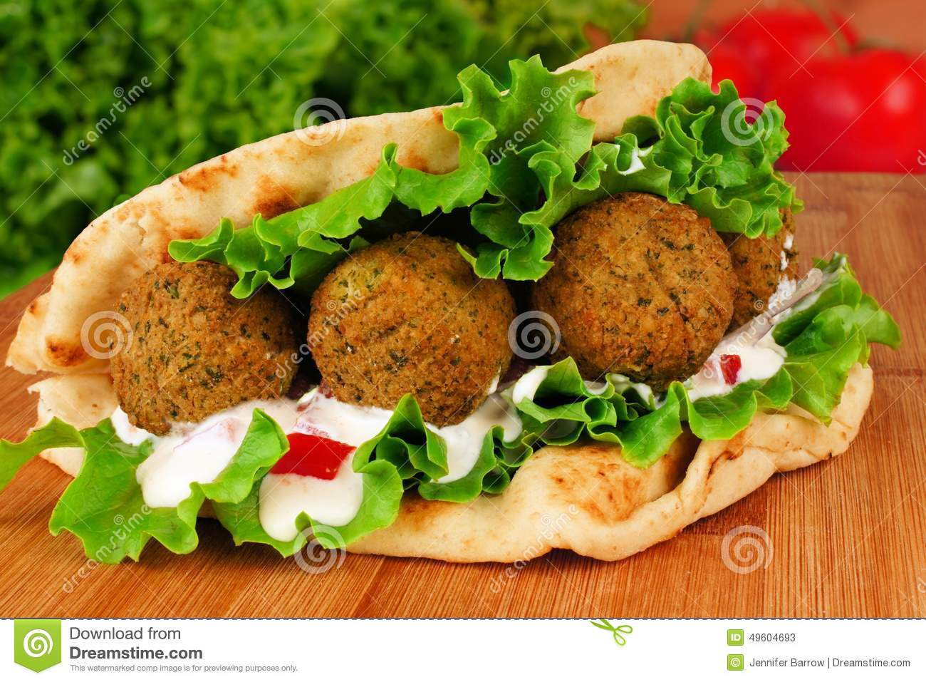 ... vegetables and tzatziki sauce in pita bread close-up on wooden table