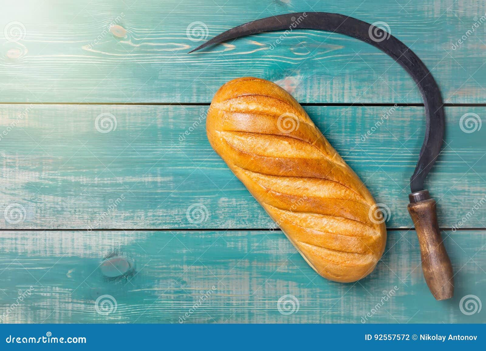 Falce d annata e pane del gancio del reaper su fondo di legno verde