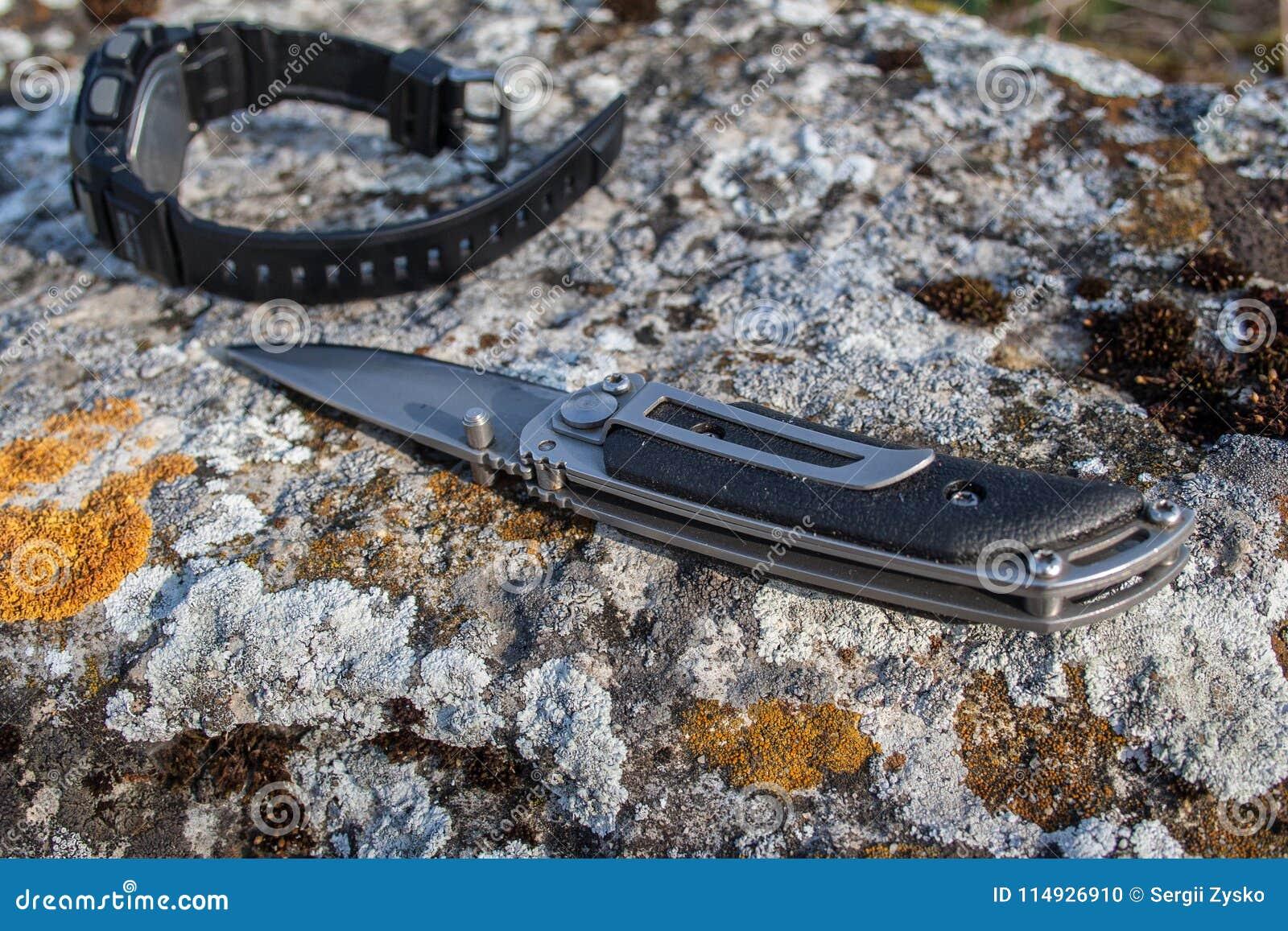 Falcowanie nóż i mężczyzna ` s zegarek na kamieniu