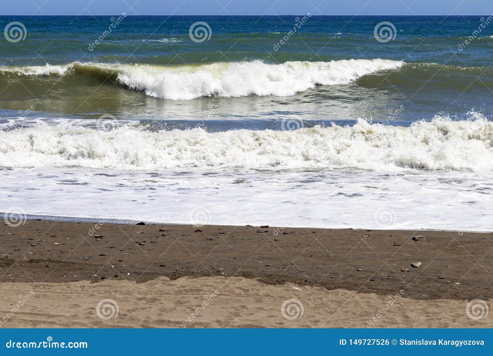 Fale na piaskowatym Costa Del Zol wyrzucać na brzeg